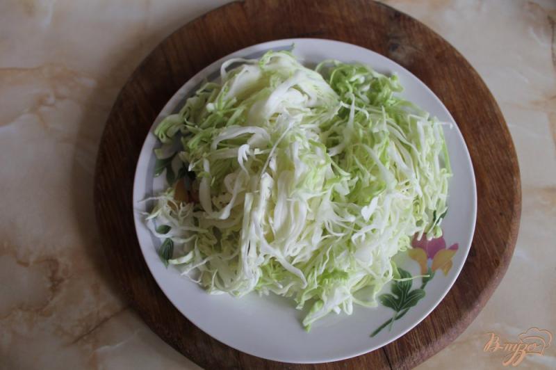 Фото приготовление рецепта: Тушеная капуста с кабачком и сосисками шаг №2