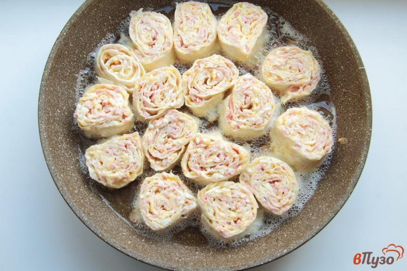 Фото приготовление рецепта: Жареные рулетики из лаваша с колбасой, сыром и яйцами шаг №10