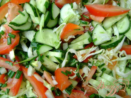 Салат с помидорами, огурцами и молодой капустой