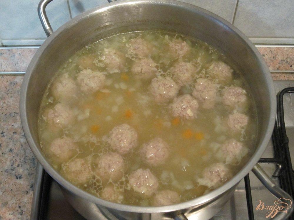 Фото приготовление рецепта: Суп с фрикадельками и зеленым горошком шаг №7